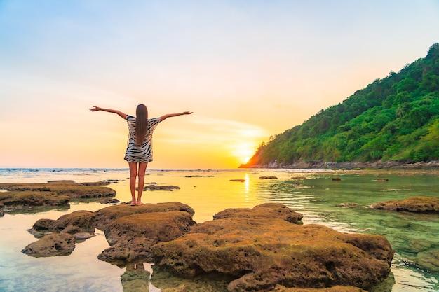 Retrato de mujer asiática en la roca con los brazos abiertos al atardecer alrededor del océano en vacaciones