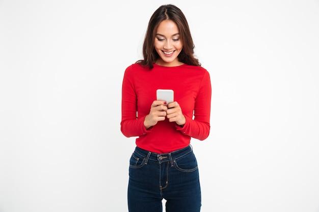 Retrato de una mujer asiática satisfecha feliz enviando mensajes de texto