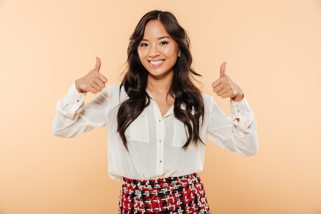 Retrato de mujer asiática sincera en casual mirando a la cámara mostrando pulgares arriba gesticulando como signo aislado sobre fondo de durazno