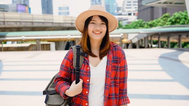 Retrato de mujer asiática sonriente joven atractiva al aire libre en la ciudad