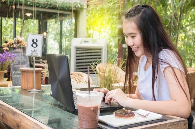 Retrato de la mujer asiática sonriente que se sienta en un café con el ordenador portátil