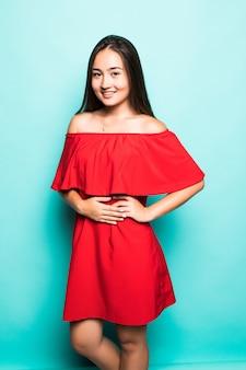 Retrato de una mujer asiática sonriente en vestido rojo de pie mirando a la cámara aislada sobre fondo turquesa