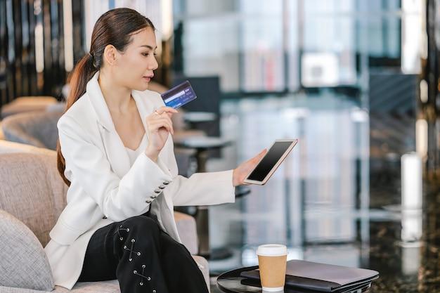 Retrato mujer asiática con tarjeta de crédito con tableta de tecnología para compras en línea en el vestíbulo moderno o trabajando, taza de café con computadora portátil, billetera de dinero de tecnología y pago en línea