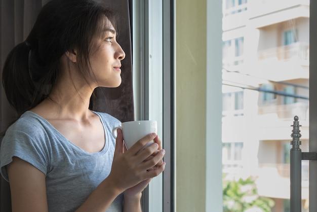 Retrato de una mujer asiática con una taza de café en la puerta del dormitorio
