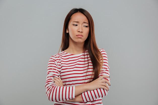 Retrato de una mujer asiática triste de pie con los brazos cruzados