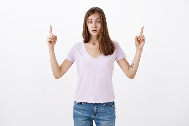 Retrato de mujer asombrada aturdida en camiseta casual con cuello en v levantando los brazos apuntando hacia arriba con asombrada mirada intensa de pie impresionado en estupor