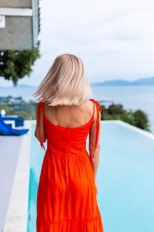 Retrato de mujer de aspecto de lujo en vestido de noche rojo anaranjado en hotel rico