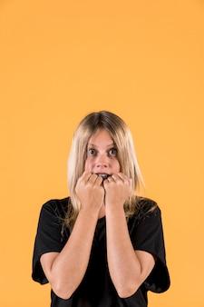 Retrato de mujer asustada de pie contra el fondo amarillo