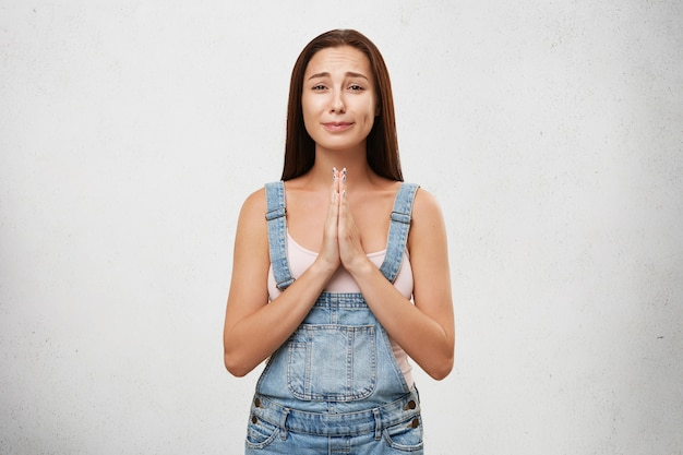 Retrato de una mujer aterradora con camisa blanca y overol de mezclilla, manteniendo las palmas juntas, llorando y pidiendo perdón. joven mujer morena con aspecto hosco aislado sobre pared blanca
