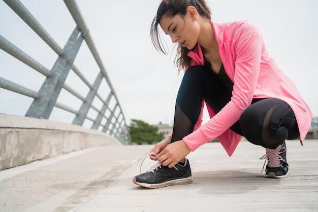 Retrato de una mujer atlética atarse los cordones de sus zapatos y preparándose para correr al aire libre. concepto de deporte y estilo de vida saludable.