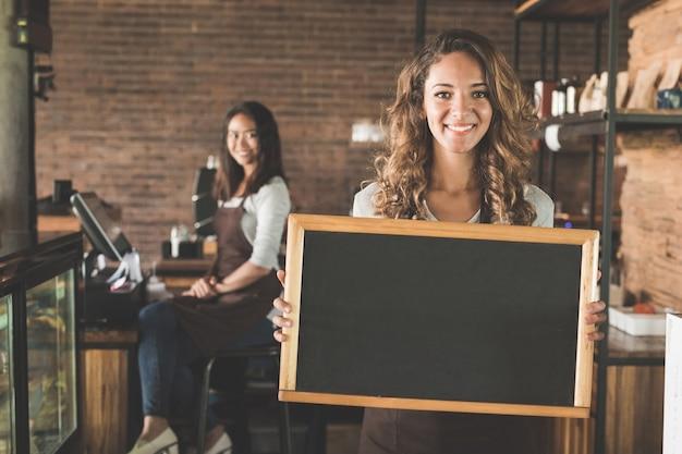 Retrato de mujer atractiva camarera de pie y sosteniendo un cartel de pizarra en blanco en un café