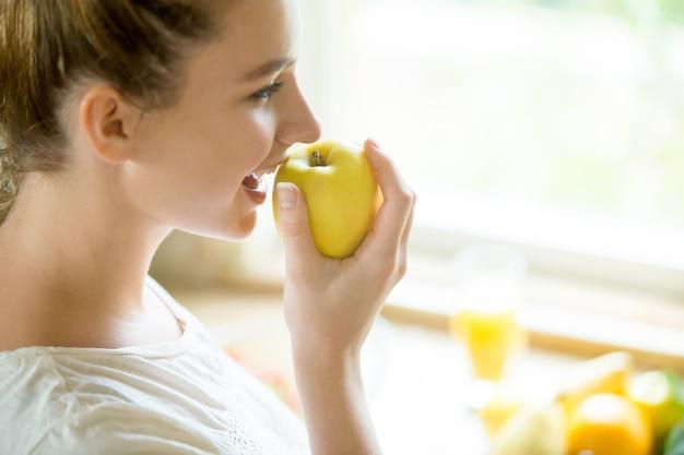 Retrato de una mujer atractiva comer una manzana