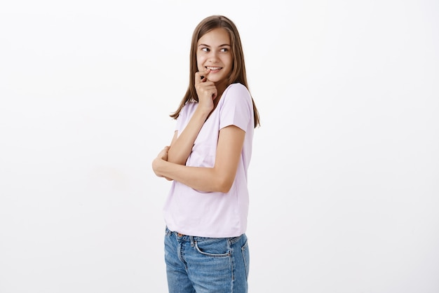Retrato de mujer atractiva femenina intrigada y coqueta con cabello largo castaño mordiendo el dedo y sonriendo con mirada curiosa girando a la derecha con intención o pensamiento en mente