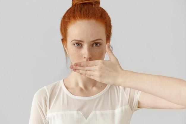 Retrato de mujer atractiva joven pelirroja cubriendo la boca con la mano