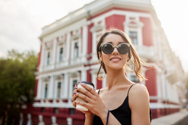 Retrato de mujer atractiva joven relajada con cabello oscuro en peinado de cola en traje negro mirando a su alrededor, esperando novio en lugar de reunión. chica sosteniendo el teléfono y bolsas de compras, caminando h