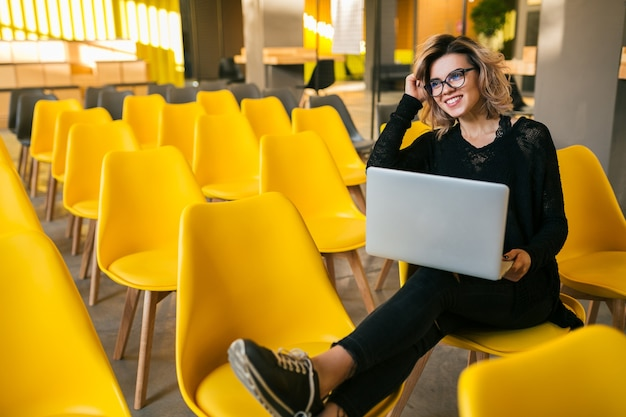 Retrato de mujer atractiva joven sentada en la sala de conferencias trabajando en un portátil con gafas, aprendizaje de los estudiantes en el aula con muchas sillas amarillas