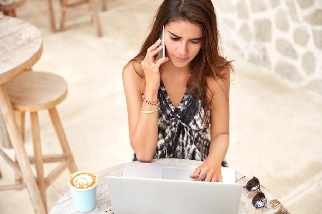 Retrato de mujer atractiva morena concentrada con expresión seria centrada en la pantalla de la computadora portátil, habla a través de un teléfono inteligente, bebe café con leche, habla con un colega en un teléfono inteligente moderno