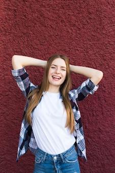 Retrato de la mujer atractiva sonriente que presenta cerca de la pared áspera