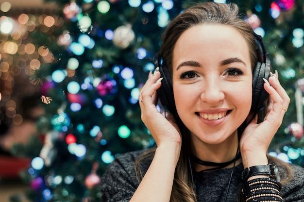 Retrato de mujer con auriculares cerca de árbol de navidad