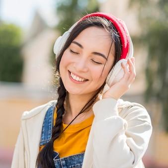 Retrato mujer con auriculares escuchando música