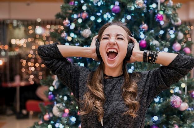 Retrato de mujer con auriculares y gritando cerca de árbol de navidad