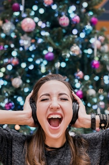 Retrato de mujer con auriculares y gritando cerca del árbol de navidad