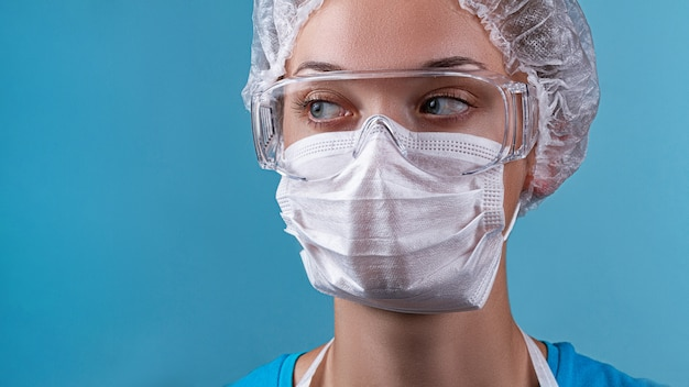Retrato de mujer auxiliar de laboratorio enfermera con gafas protectoras de medicina, máscara médica facial durante la epidemia de gripe covid-19. ropa de médicos y protección contra virus en el brote de coronavirus
