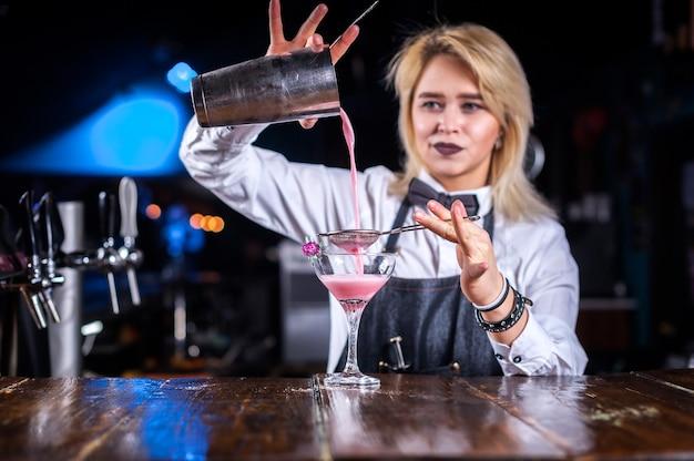 Retrato de mujer barman demuestra sus habilidades en el mostrador de la discoteca
