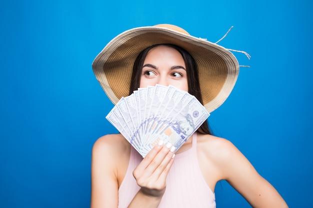 Retrato de mujer bastante encantadora que cubre la mitad de la cara de cierre con ventilador de dólares mirando con ojos a la cámara aislada en la pared azul.