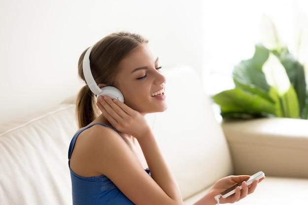 Retrato de la mujer bastante joven en los auriculares que se sientan en el sofá