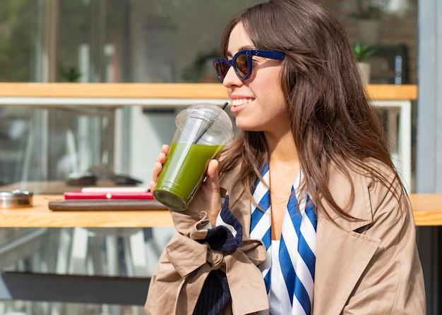 Retrato de mujer bebiendo batido verde