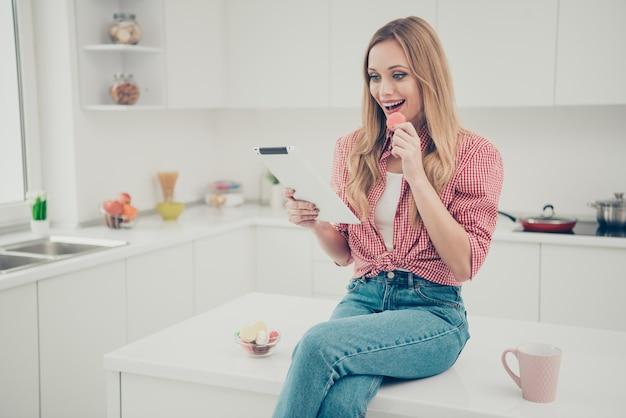 Retrato mujer bebiendo té y comiendo macarrones