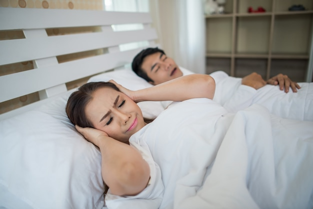 Retrato de mujer bloqueando orejas con hombre durmiendo ronquidos en cama