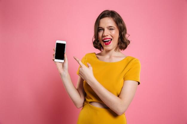 Retrato de una mujer bonita alegre que señala el dedo en blanco