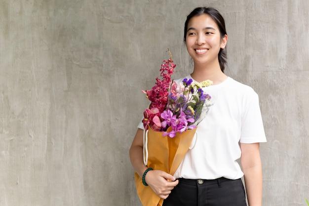 Retrato de la mujer bonita alegre que sostiene las flores sobre fondo gris.