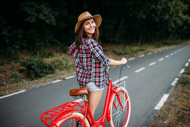 Retrato de mujer bonita con bicicleta vintage roja