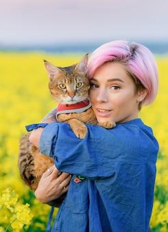 Retrato de mujer bonita con cabello rosado, descansando sobre la naturaleza, sosteniendo el gato en sus brazos y mirando a la cámara