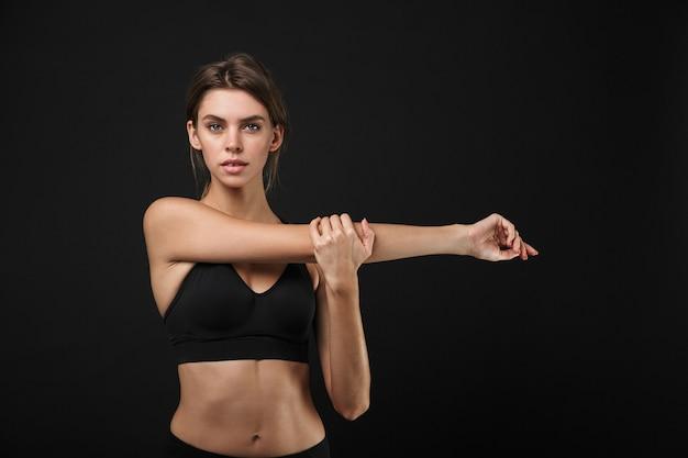 Retrato de mujer bonita caucásica en ropa deportiva estirando sus brazos durante el entrenamiento en el gimnasio aislado sobre fondo negro