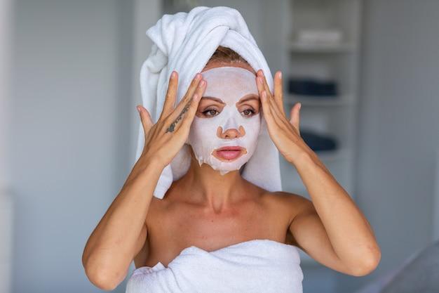 Retrato de mujer bonita caucásica tranquila con una toalla en la cabeza y una máscara cosmética en la cara concepto de cuidado de la piel de la cara mujer relajarse en la cama en casa