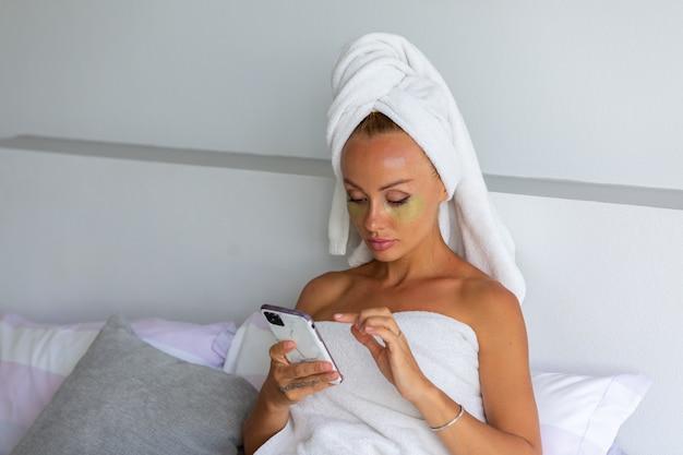 Retrato de mujer bonita caucásica tranquila con una toalla en la cabeza y parches de máscara para los ojos en la cara concepto de cuidado de la piel de la cara mujer relajarse en la cama en casa tomar selfie teléfono
