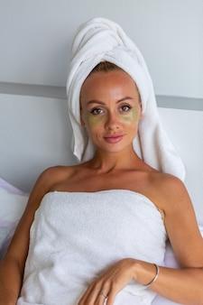 Retrato de mujer bonita caucásica tranquila con una toalla en la cabeza y parches de máscara para los ojos en la cara concepto de cuidado de la piel de la cara mujer relajarse en la cama en casa
