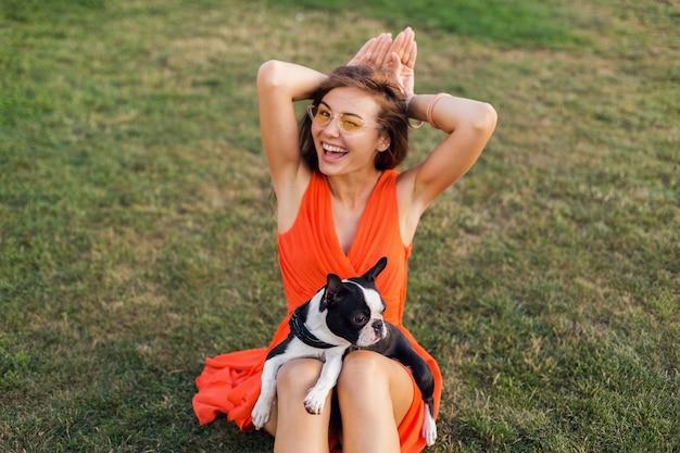 Retrato de mujer bonita feliz sentada en el césped en el parque de verano, sosteniendo el perro boston terrier, humor positivo sonriente, vestido naranja, estilo moderno, gafas de sol, jugando con mascota