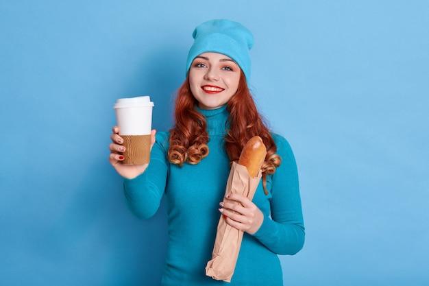 Retrato de mujer bonita con gorra y suéter casual, sonriendo sinceramente