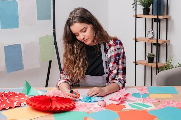 Retrato de mujer bonita haciendo origami creativo trabajo de arte