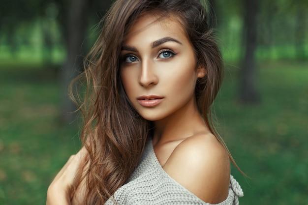 Retrato de una mujer bonita con increíbles ojos azules con el peinado en el parque.
