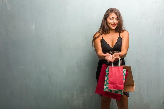 Retrato de una mujer bonita joven que lleva un vestido contra una pared que sostiene algo con las manos