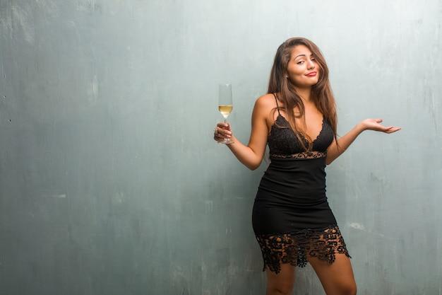 Retrato de mujer bonita joven con un vestido contra una pared dudando y encogiéndose de hombros