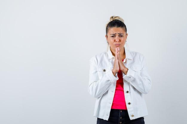 Retrato de mujer bonita manteniendo las manos en gesto de oración en chaqueta blanca y mirando triste vista frontal