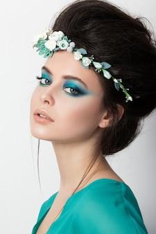 Retrato de mujer bonita morena en vestido turquesa y diadema de flores