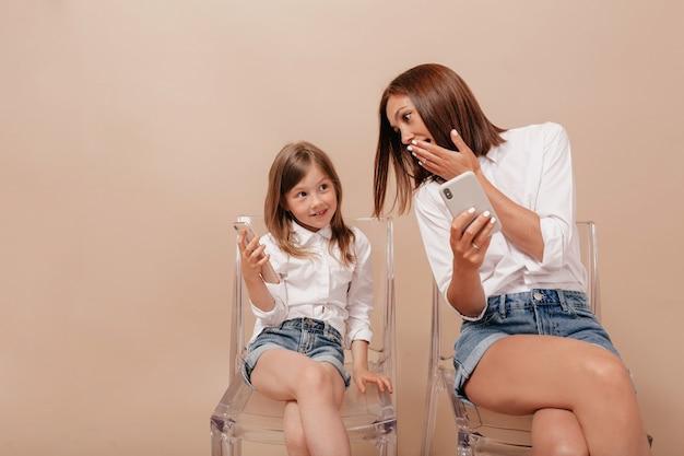 Retrato de mujer bonita con niña encantadora sentada en sillas con teléfonos inteligentes y discutiendo algo